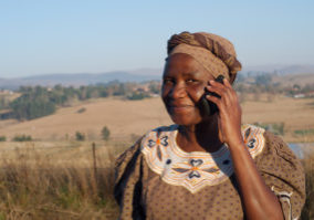 Traditional African Zulu woman speaking on mobile cell phone telephone in rural KwaZulu-Natal.