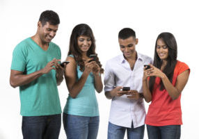 Group of young Indian friends using their smartphones. Happy Asian people using their cell phones. Isolated on white background.