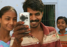 Man with daughters taking a video.