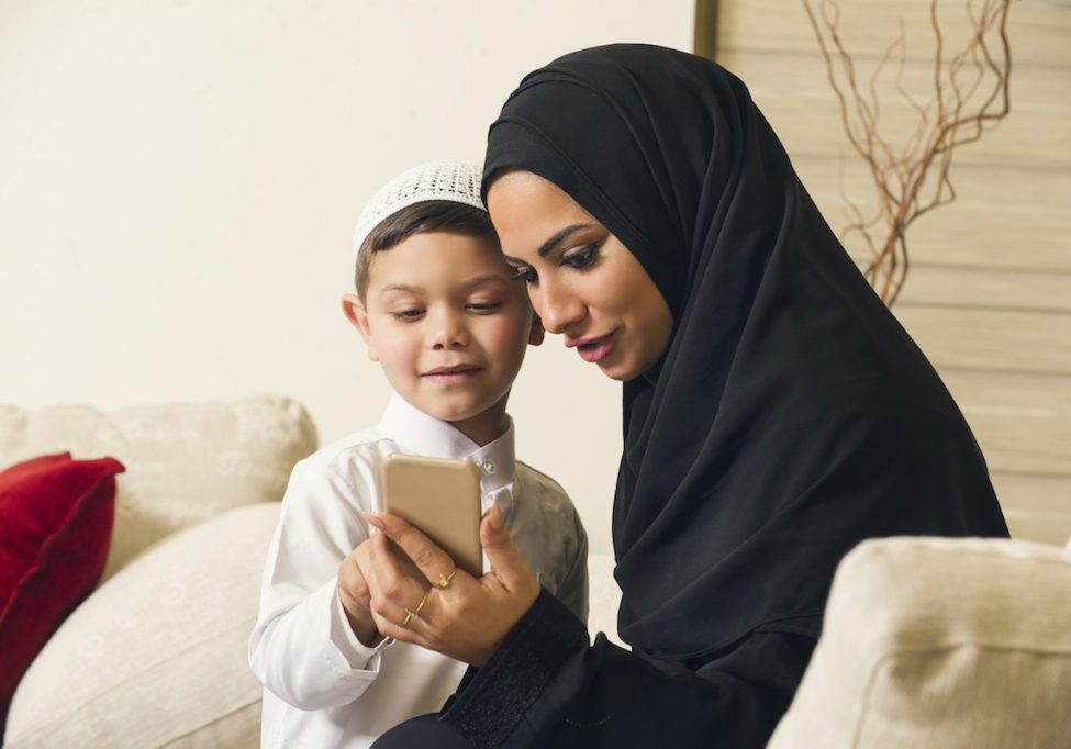 Muslim mother and son using mobile phone.